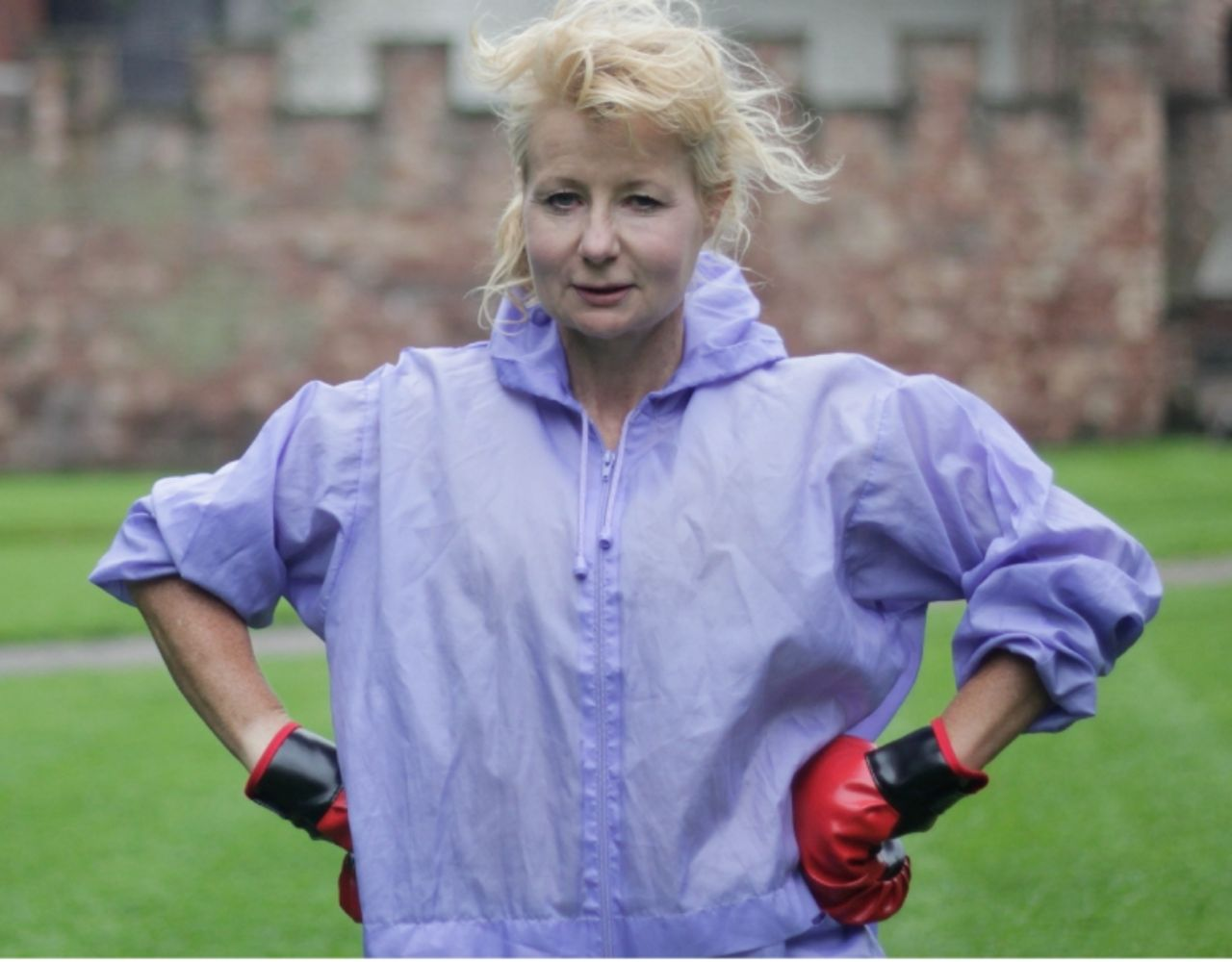 Woman standing in a field with boxing gloves on.